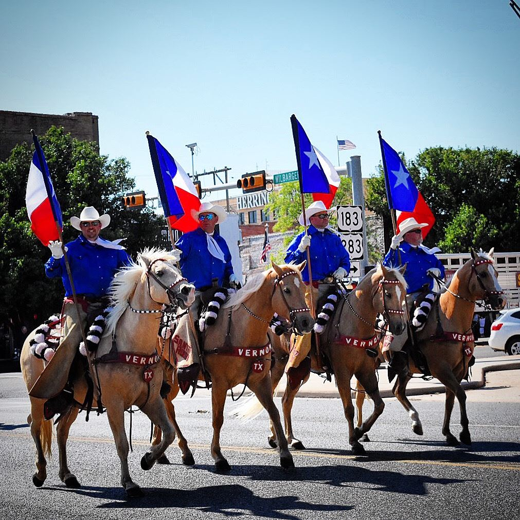 Men riding palomino horses in a parade